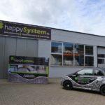 Firmenwagen von happySystem und Außenansicht der Werkshalle